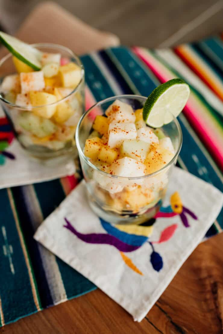 two glasses filled with mango jicama cucumber salad on two Mexican cocktail napkins on a colorful striped runner