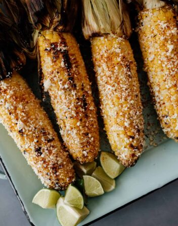 4 pieces of Mexican street corn on a serving platter
