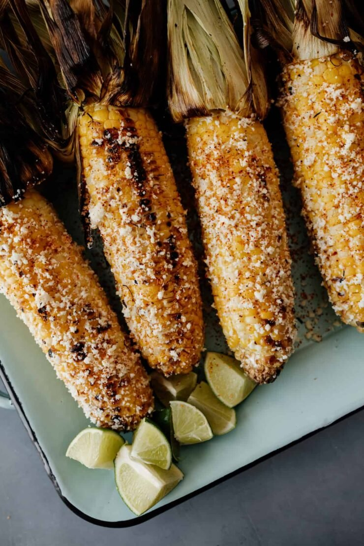 4 cobs of corn that have been turned into elote on a teal rectangular serving dish with lime wedges