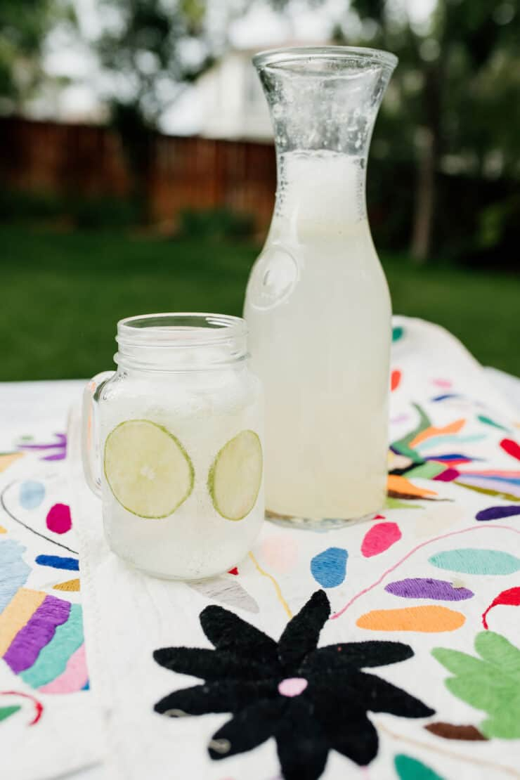mason jar with a handle filled with sparkling limeade and round lime slices on a picnic blanket next to a carafe of limonada