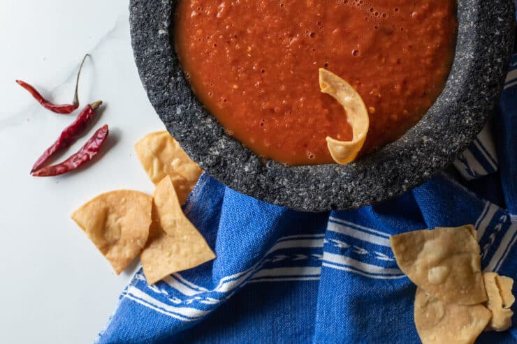 overhead shot of a bowl of chile de arbol spicy salsa with a blue and white tea towel and crispy tortilla chips