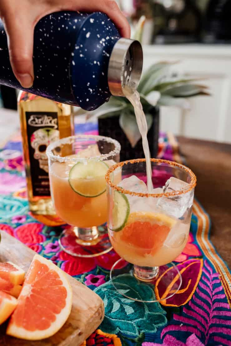 blue cocktail shaker pouring a Paloma in a cocktail glass prepped with Tajin and Salt with reposado tequila next to fresh grapefruit and lime wedges on a colorful Mexican flowered textile