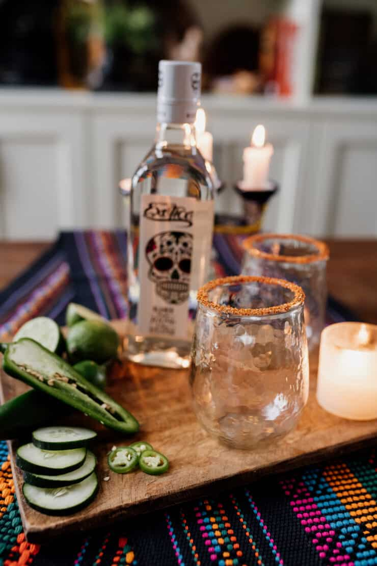 cocktail glasses rimmed with Tajin and tequila bottle in the background and candles