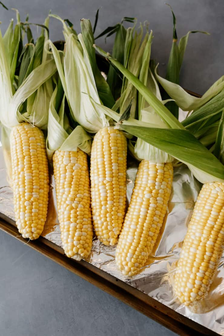 corn on the cob with husks pulled back but not removed prior to grilling