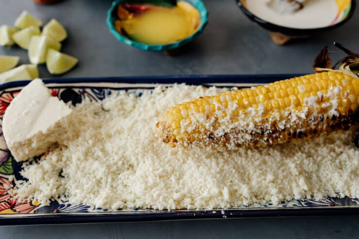 rolling elote in cotija cheese