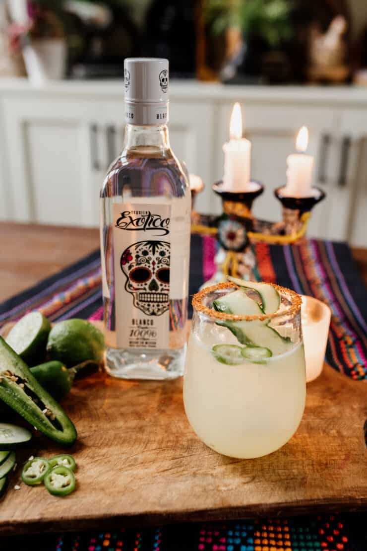Exotico Tequila bottle with a spicy cucumber cocktail and candles