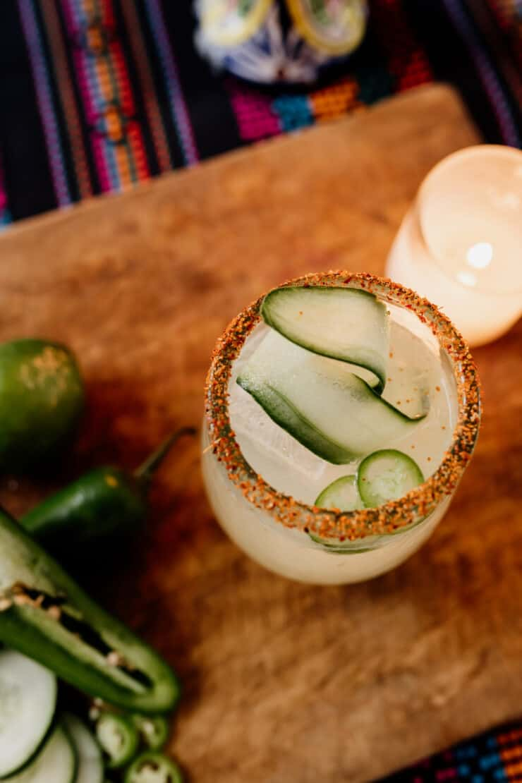 cucumber jalapeño margarita in cocktail glasses on a brown board and candle in background