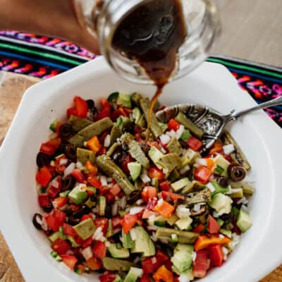 pouring dressing onto grilled nopales salad