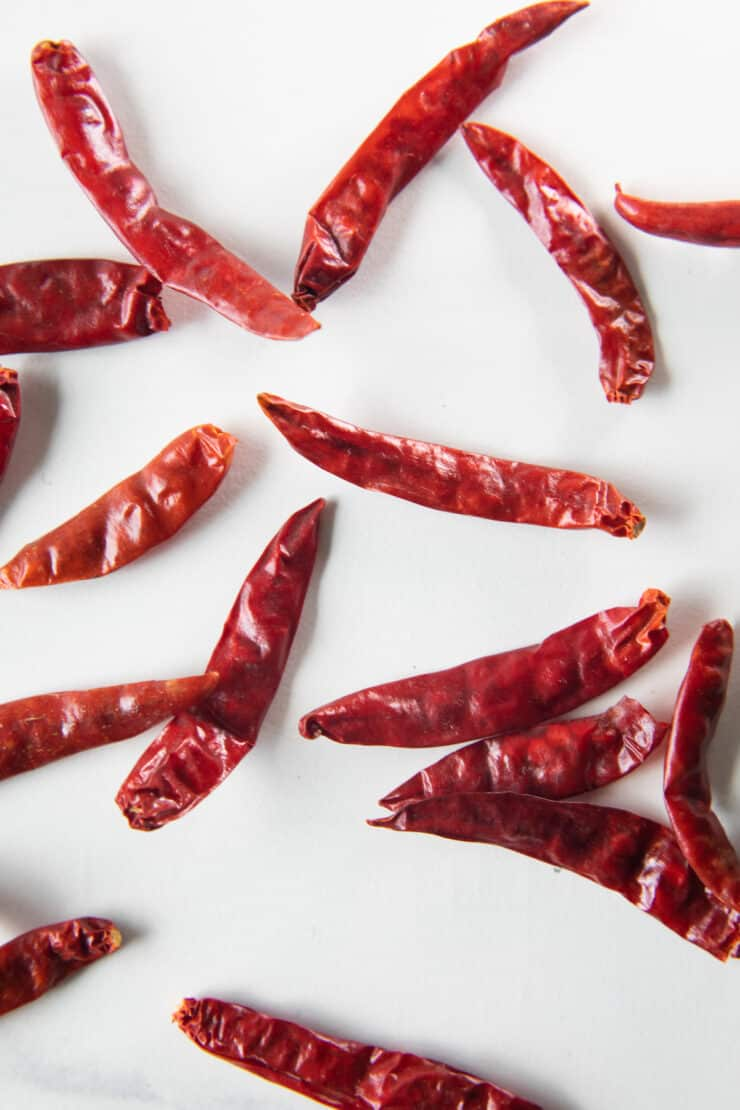 chiles de arbol on a white surface