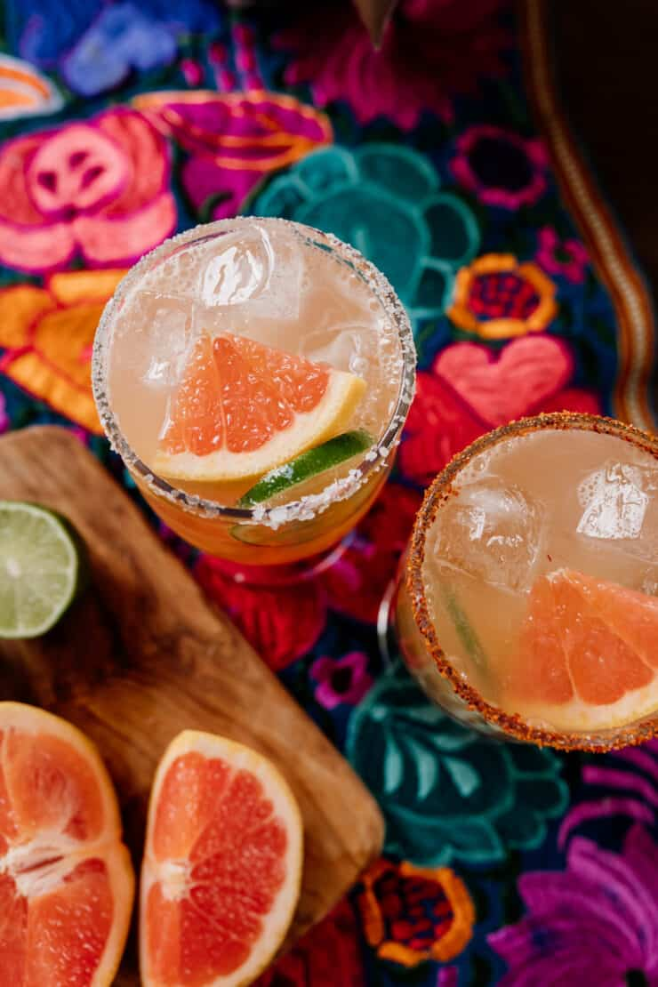 top down shot of two cocktail glasses prepped with Tajin and Salt with reposado tequila next to fresh grapefruit and lime wedges on a colorful Mexican flowered textile