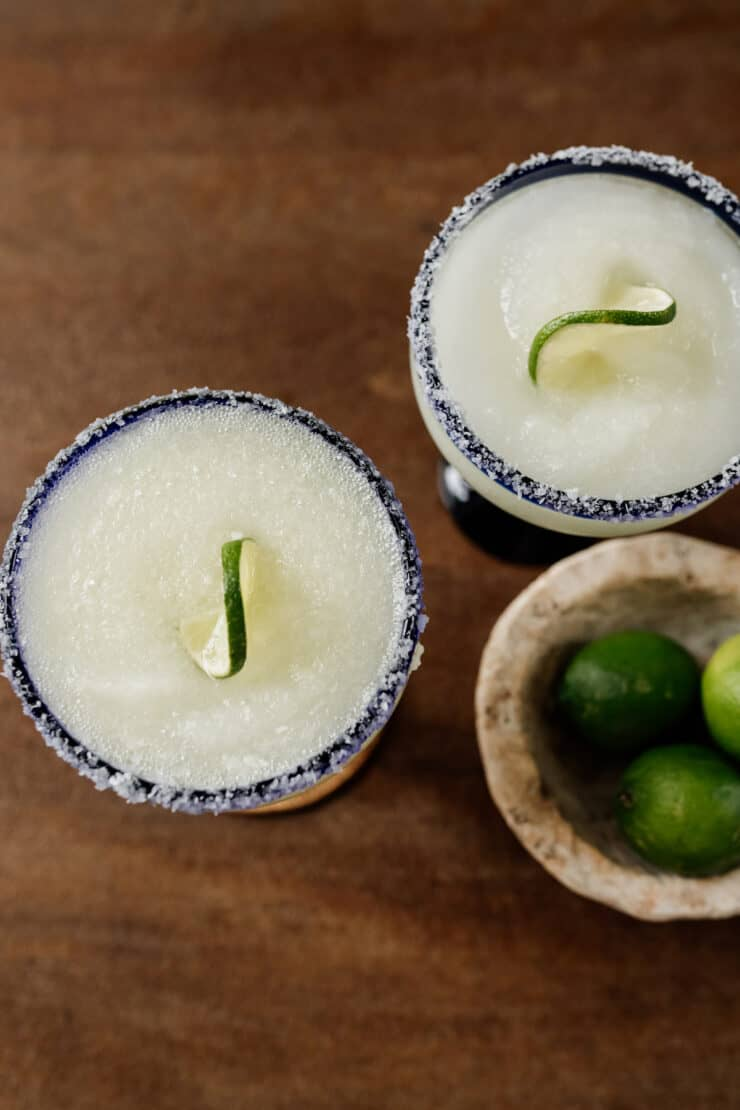 two Classic Frozen Margaritas with slated rimmed glasses top down with a side of limes