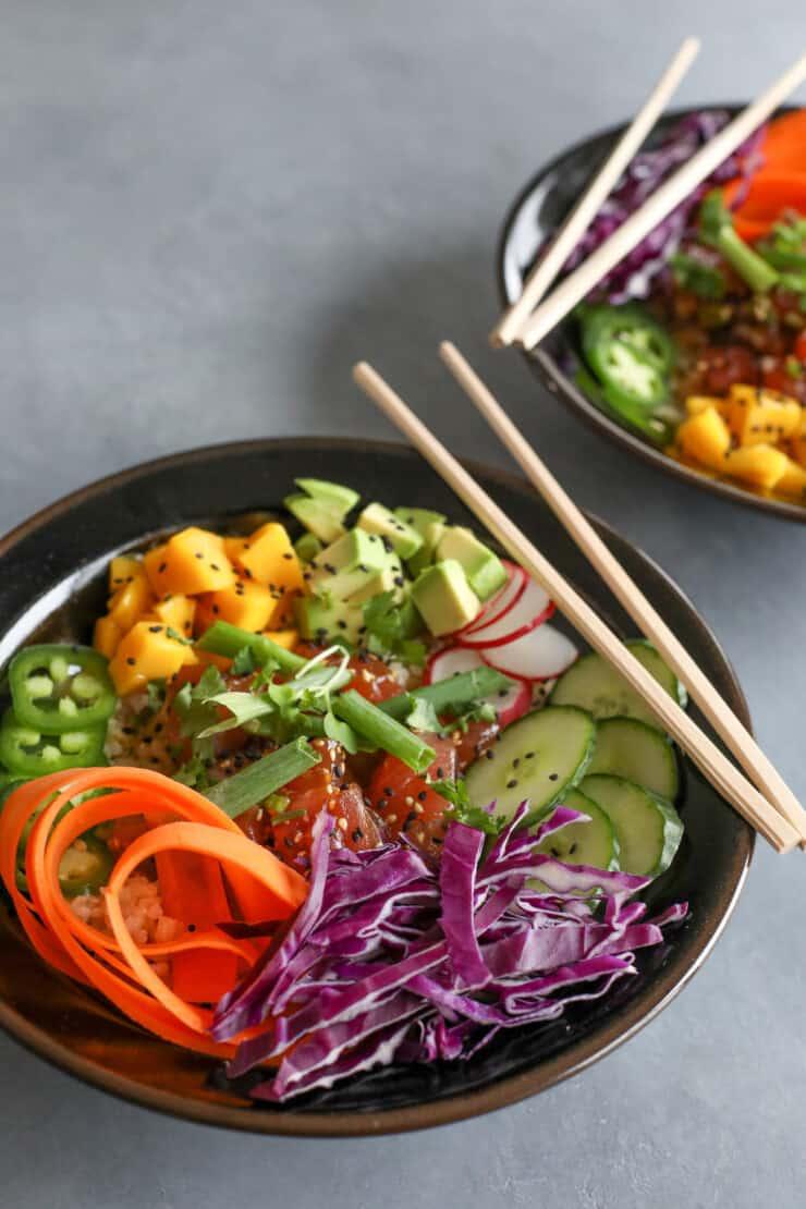 black bowl of spicy tuna poke with fresh veggies and brown sushi rice