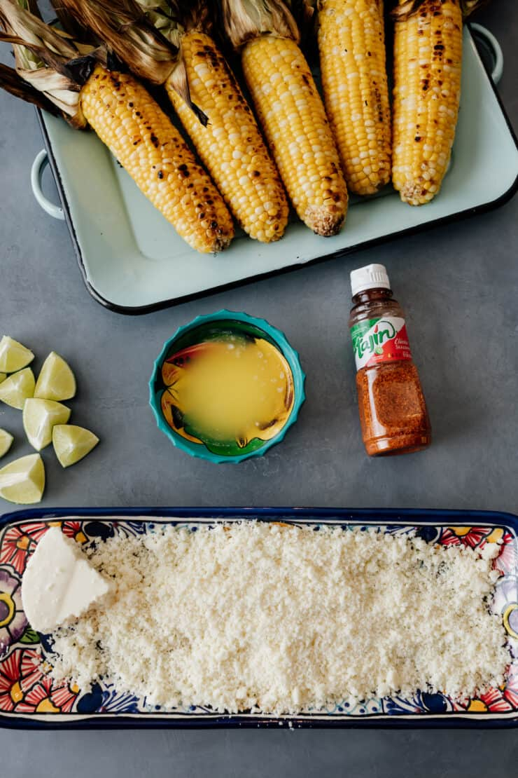 overhead shot of grilled corn on the cob with the fixings for making it into elote laid out on a grey table