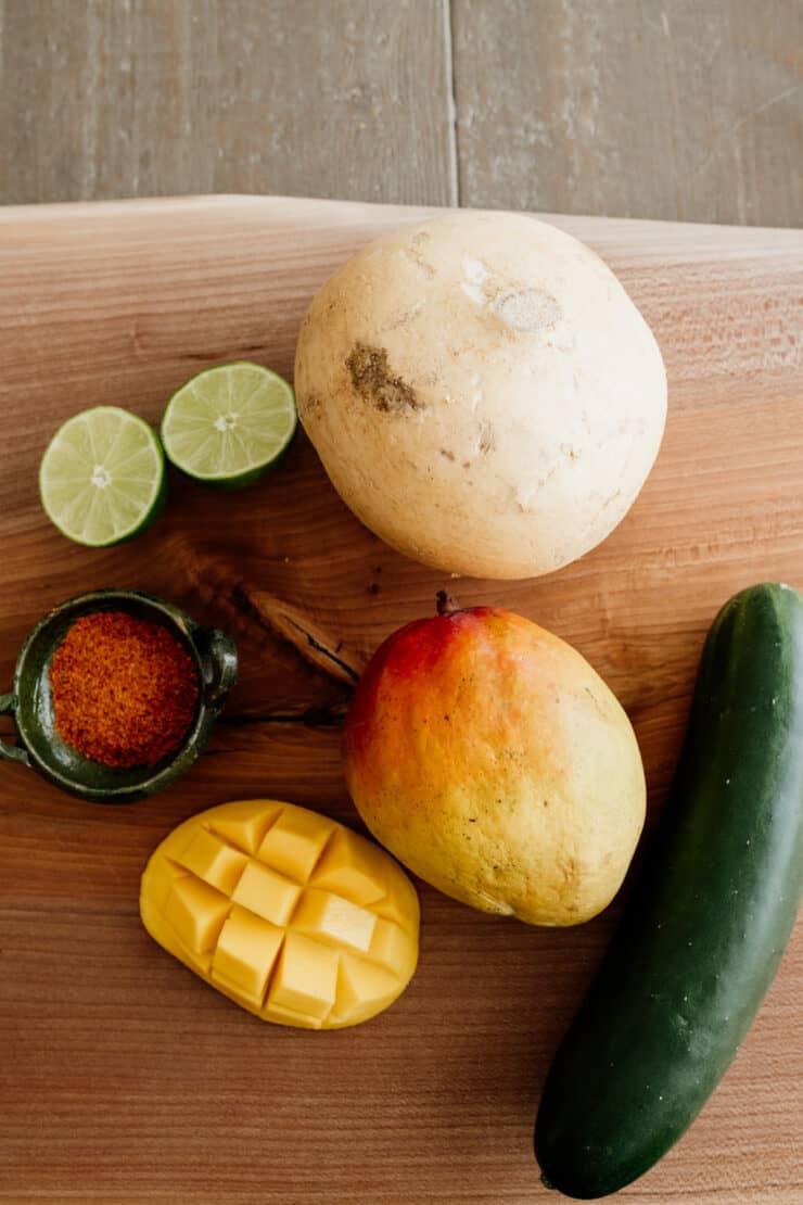 jicama two mangos lime cut in half a cucumber and a small green bowl of tajin