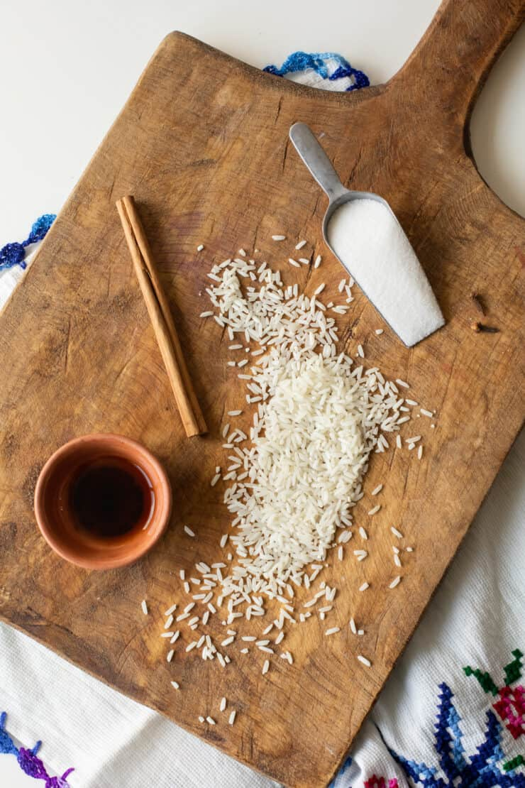 wooden cutting board with vanilla, cinnamon stick, rice and sugar laid out for homemade horchata recipe