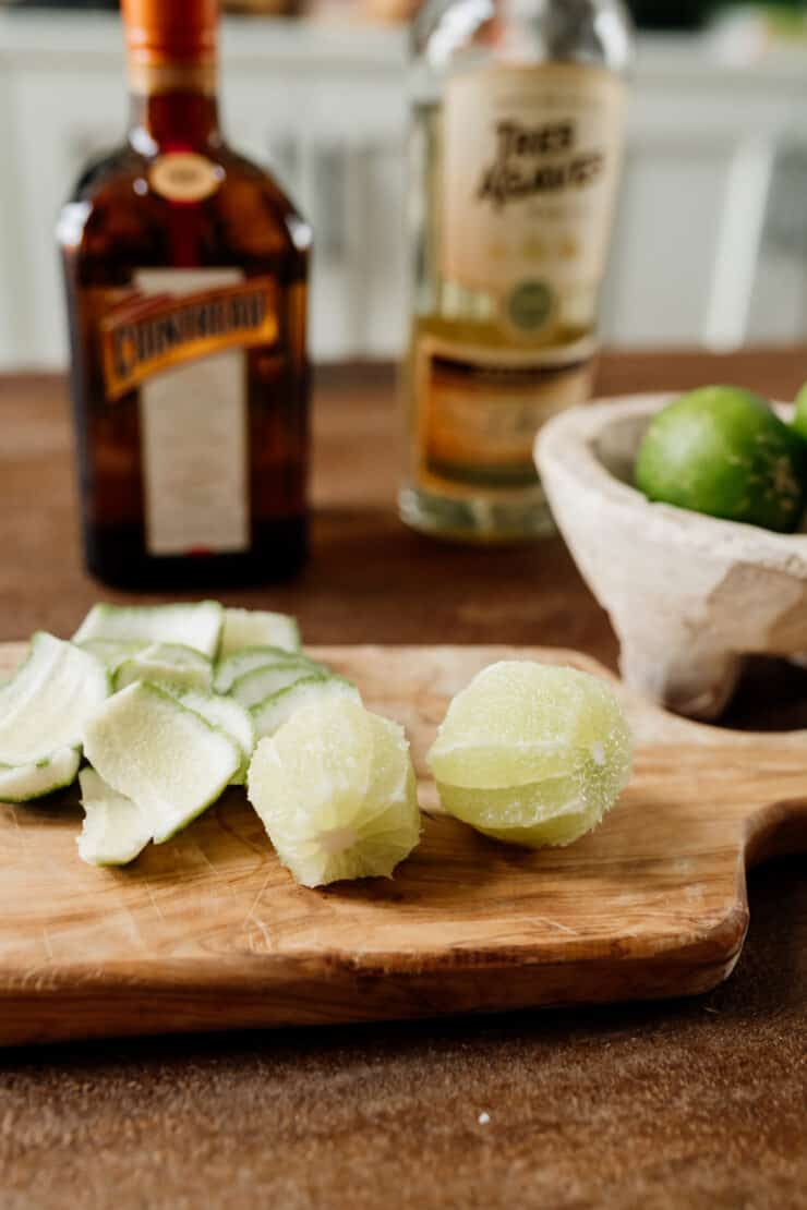 two limes peeled with margarita ingredients in the background