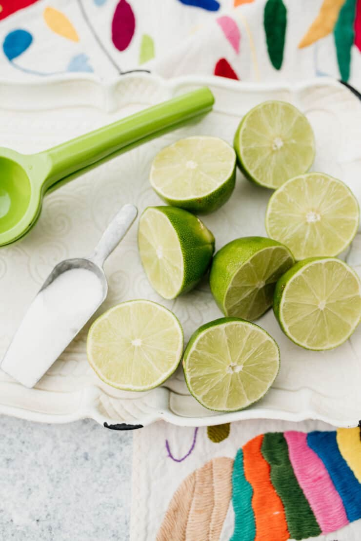 halved limes on a platter next to a citrus juicer