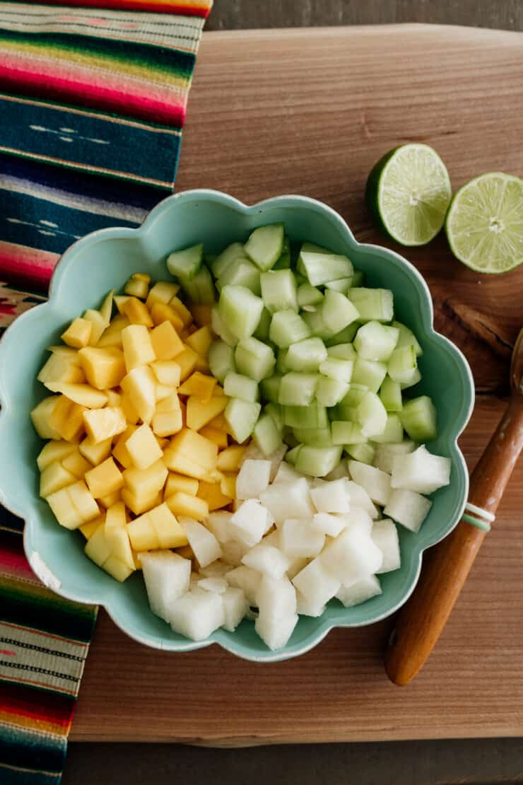 turquoise bowl with chopped mango jicama and cucumber on a striped runner and brown table