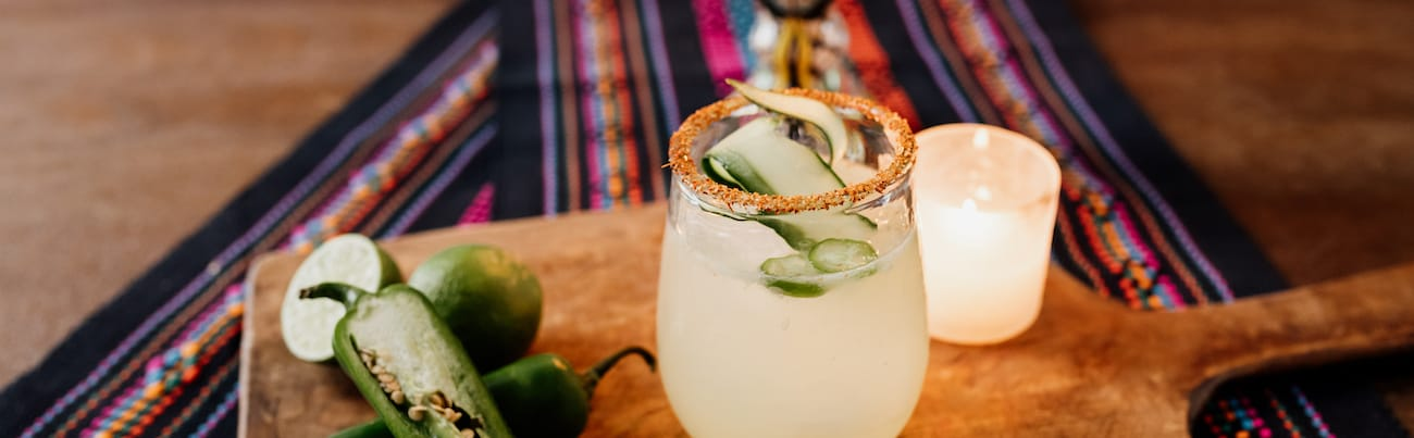 cucumber margarita with a spicy rim on a wooden board and small white candle on a colorful striped textile