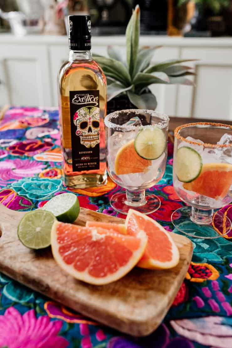 two cocktail glasses prepped with Tajin and Salt with reposado tequila next to fresh grapefruit and lime wedges on a colorful Mexican flowered textile