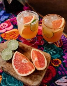 two Paloma cocktails with fresh citrus on the side