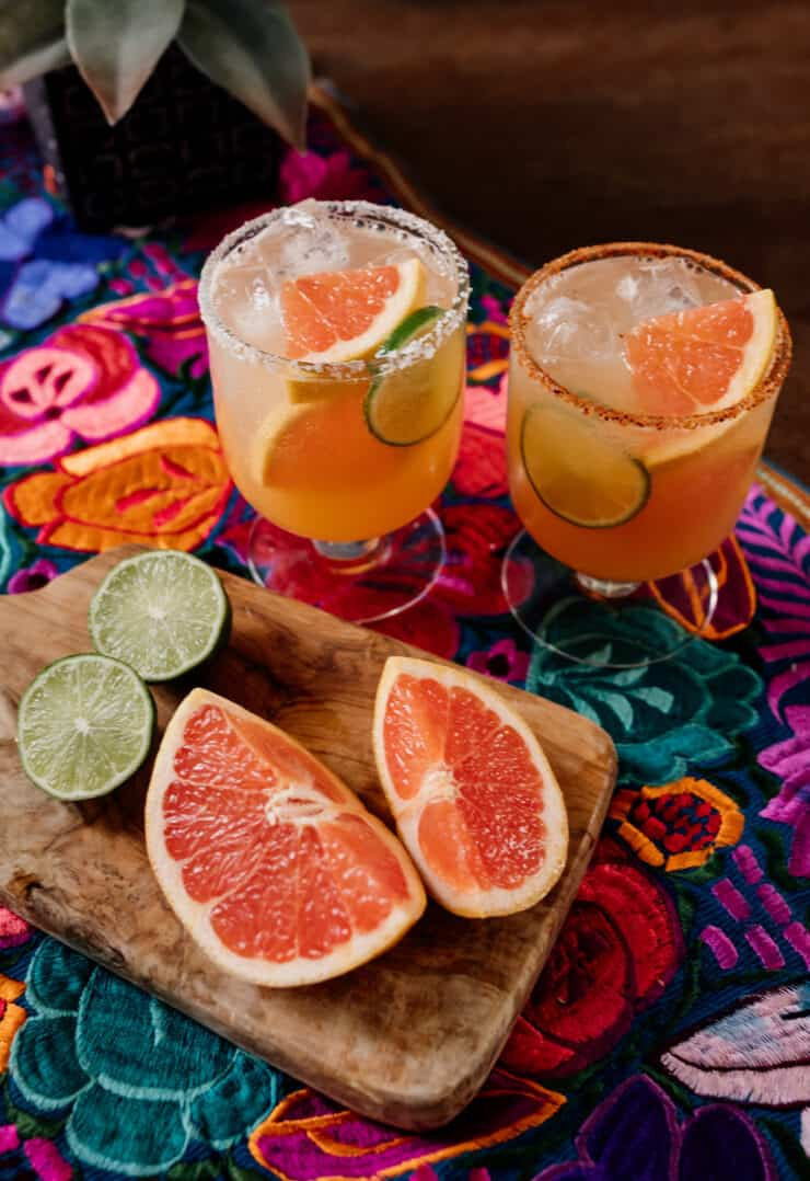 two cocktail glasses filled with reposado palomas next to fresh grapefruit and lime wedges on a colorful Mexican flowered textile