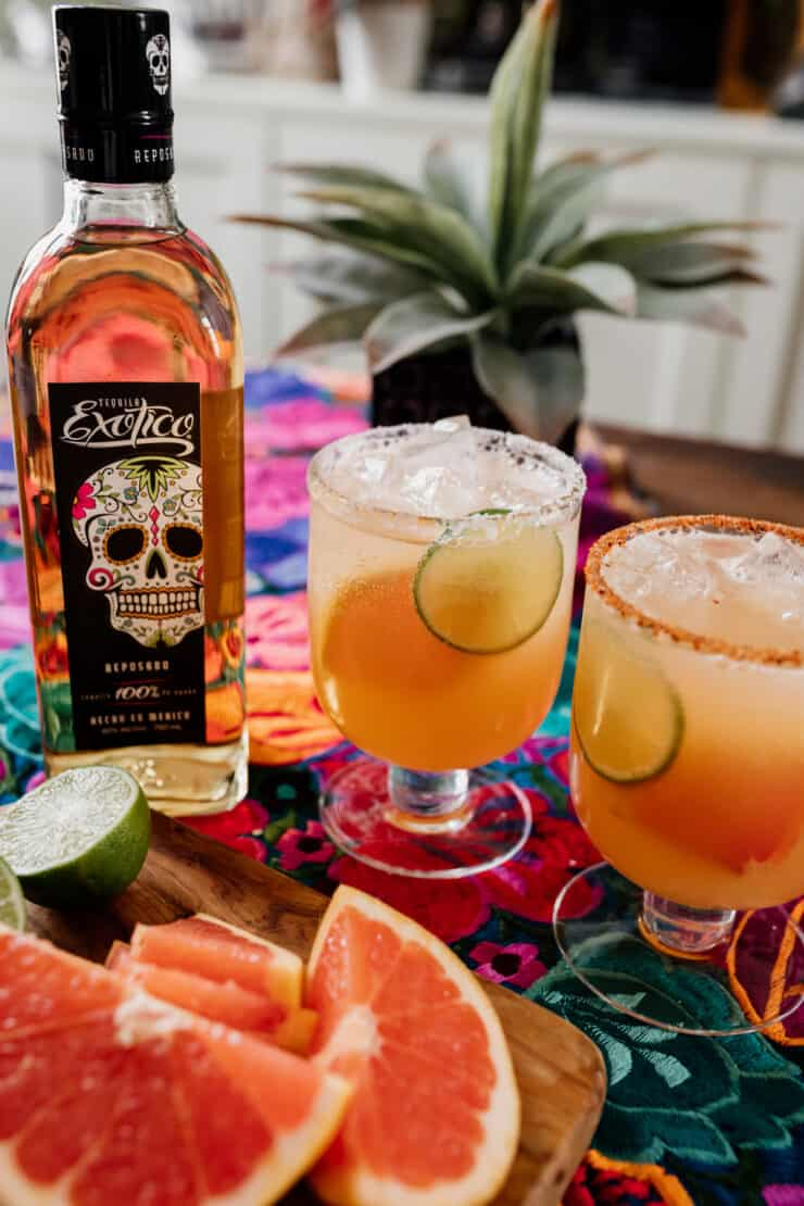 two sparkling Paloma cocktails with Exotico Tequila bottle in the background
