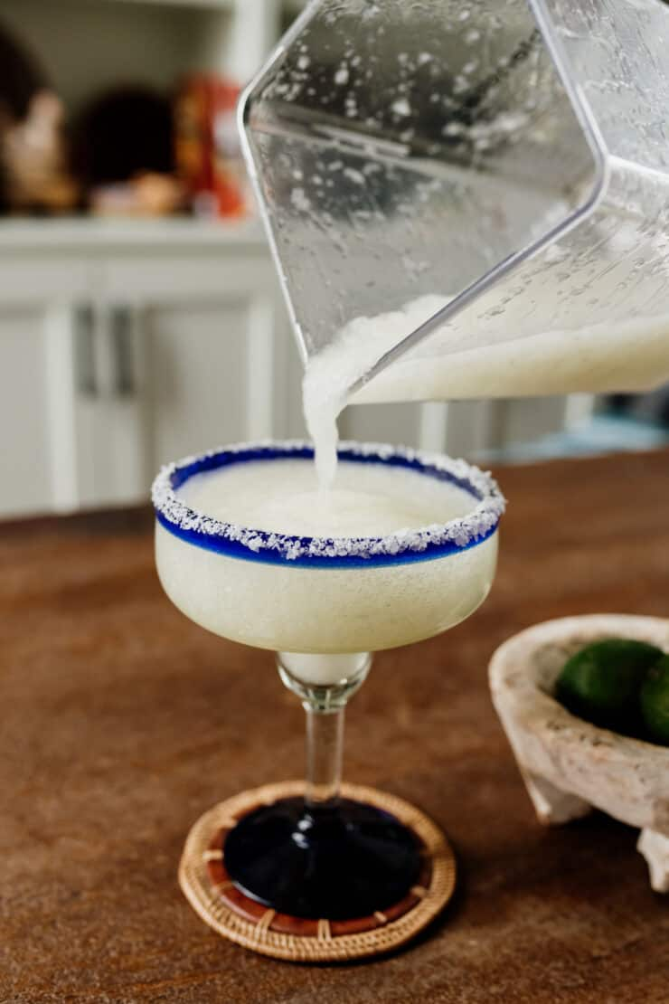 blended frozen margarita being poured into a margarita glass