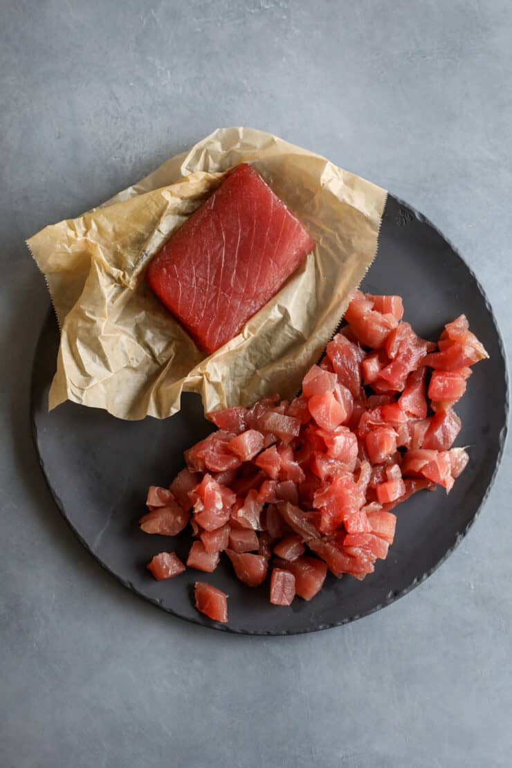 hunk of raw tuna on a piece of parchment next to cubes of tuna on a slate plate