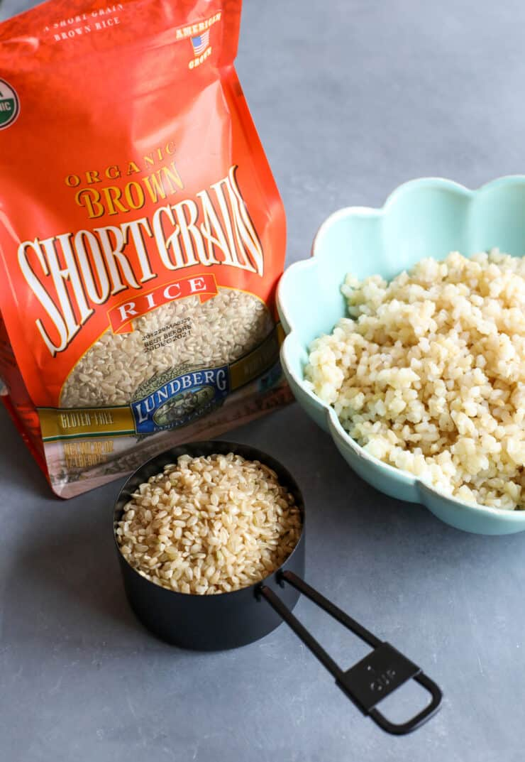 bag of lundberg brown short grain rice with a measuring cup of dried rice next to a bowl of cooked rice