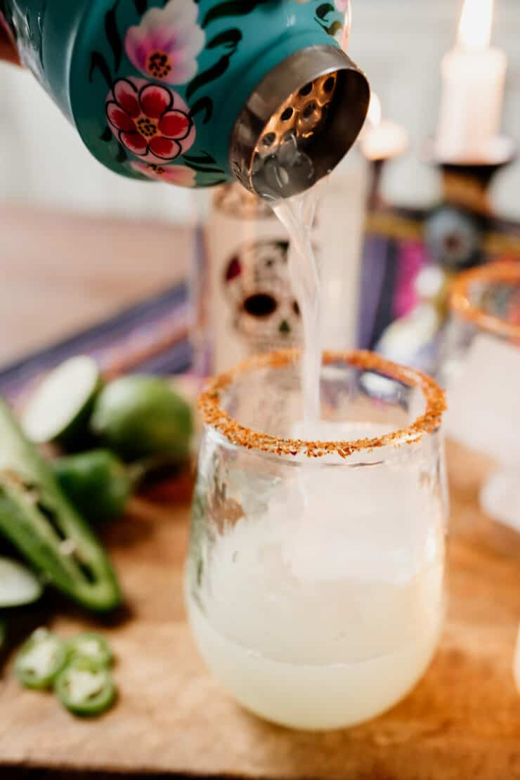 pouring a cucumber margarita into a cocktail glass rimmed with Tajin and filled with ice
