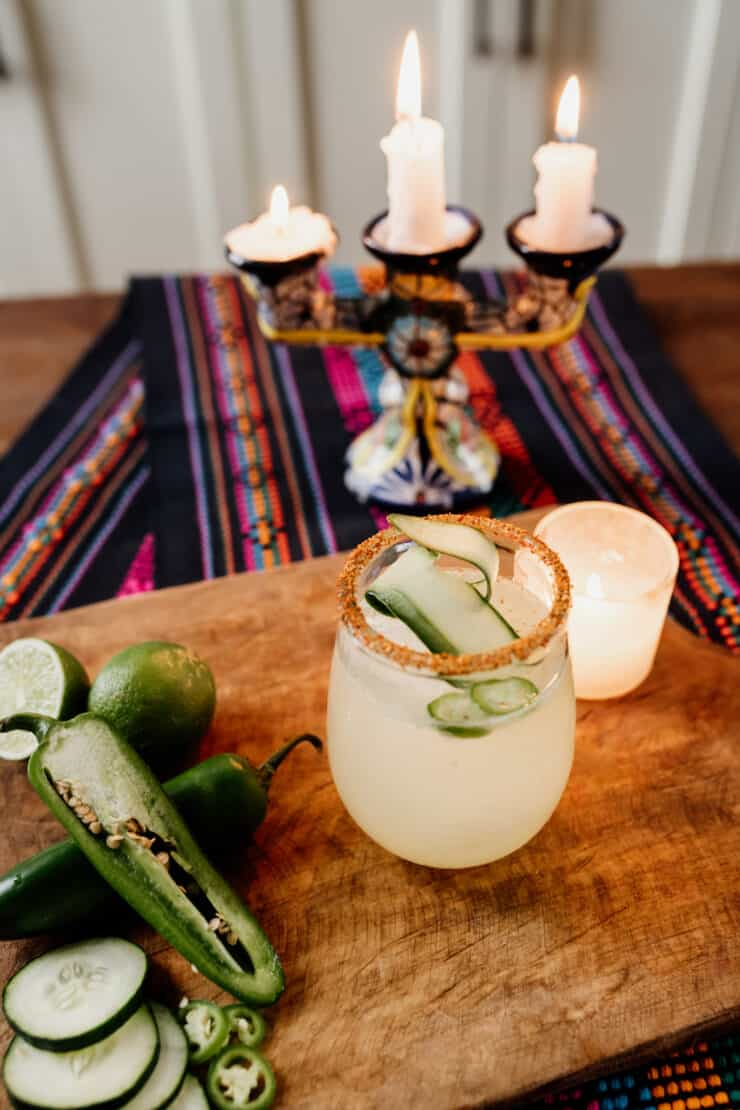 a cucumber margarita on a wooden board and fresh ingredients beside it and candles in the background