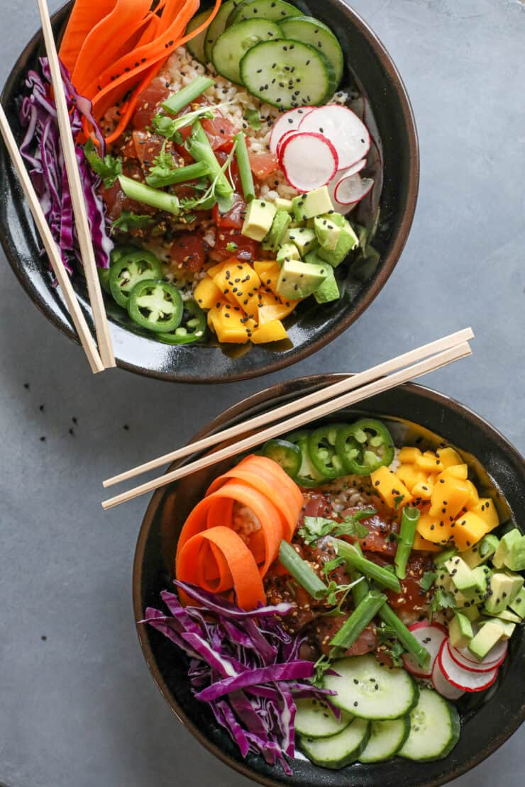 overhead shot of two bowls filled with spicy tuna poke and all the fixings