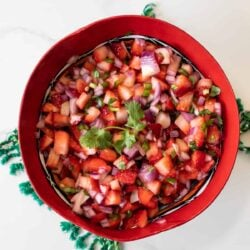 overhead shot of a red bowl filled with strawberry salsa