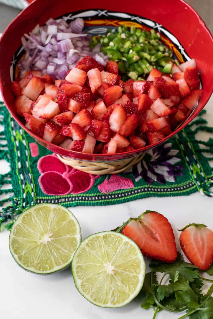 ingredients for strawberry pico de gallo salsa in a red mixing bowl on a green embroidered textile