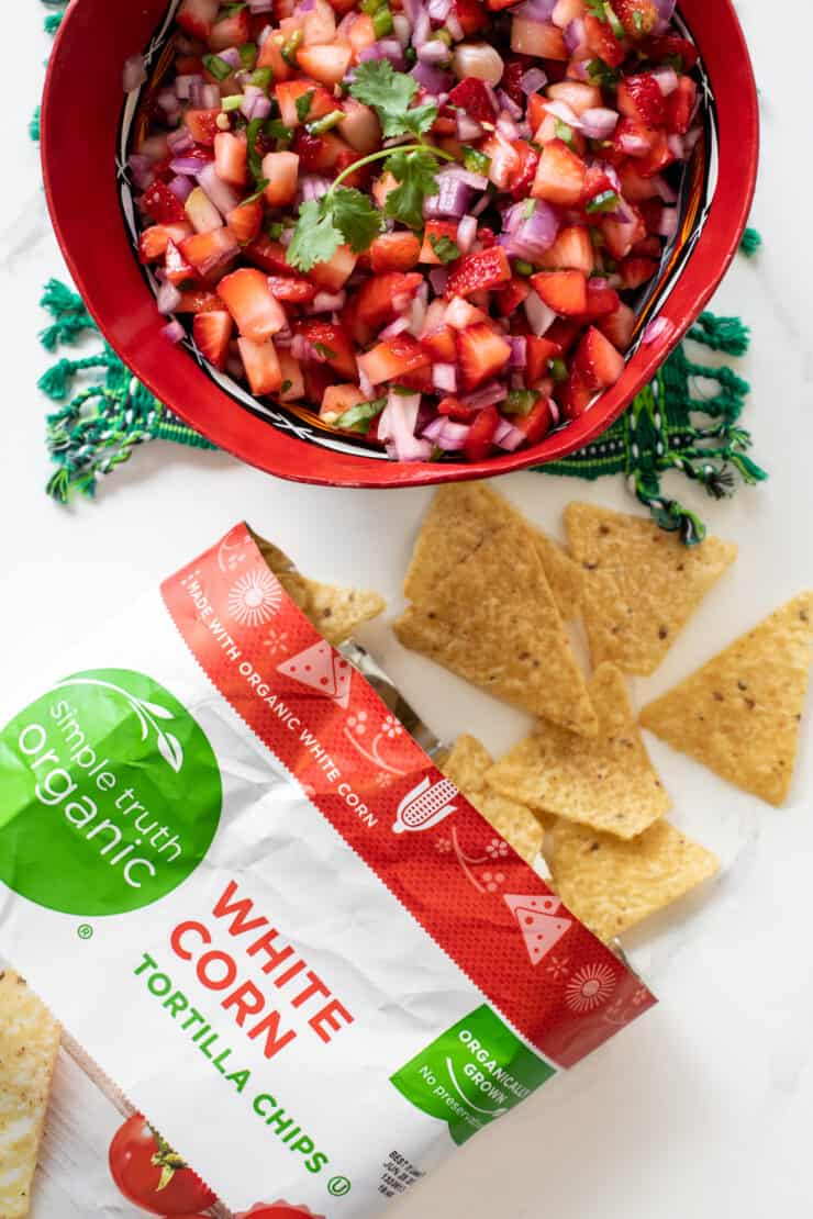 overhead shot of a bowl of strawberry salsa next to a bag of simple truth organic corn tortilla chips