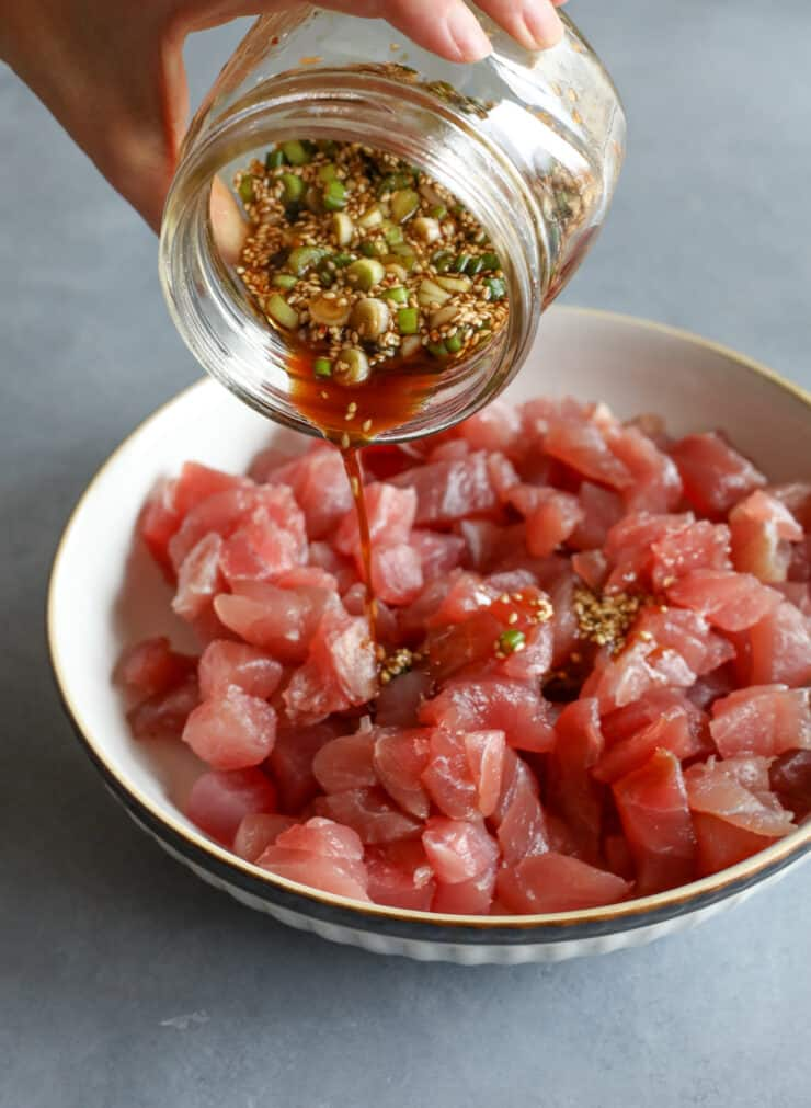 hand pouring jar of sushi marinade over tuna chunks to make spicy poke
