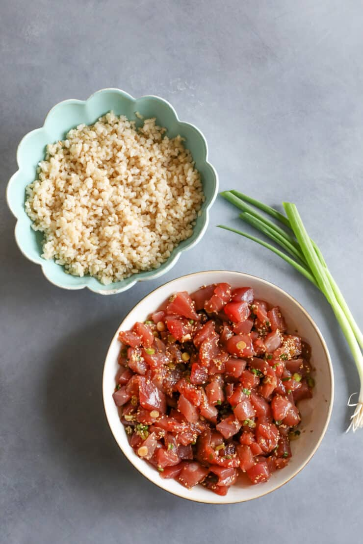 overhead shot of spicy tuna poke mix in a bowl next to a bowl of cooked brown rice