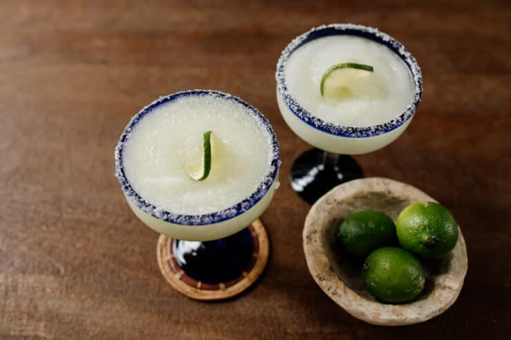 two frozen margarita glasses on a brown table with a bowl of limes on the side