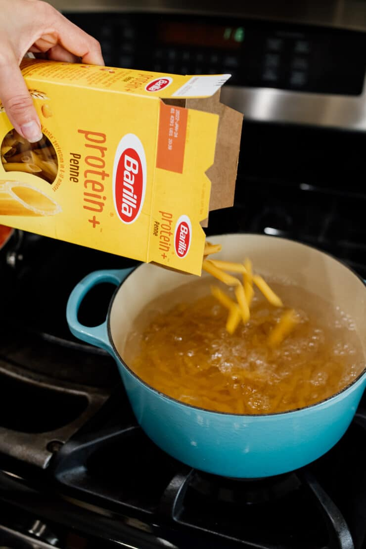 Barilla protein pasta box being poured into a pot of boiling water