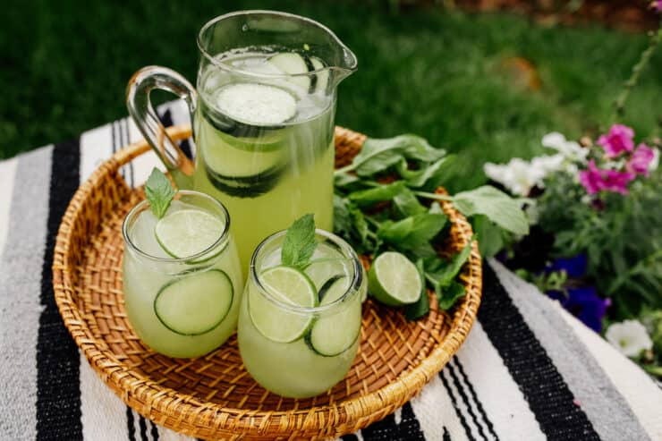 picnic blanket on the grass with a rattan serving tray filled with glasses and a pitcher of cucumber agua fresca