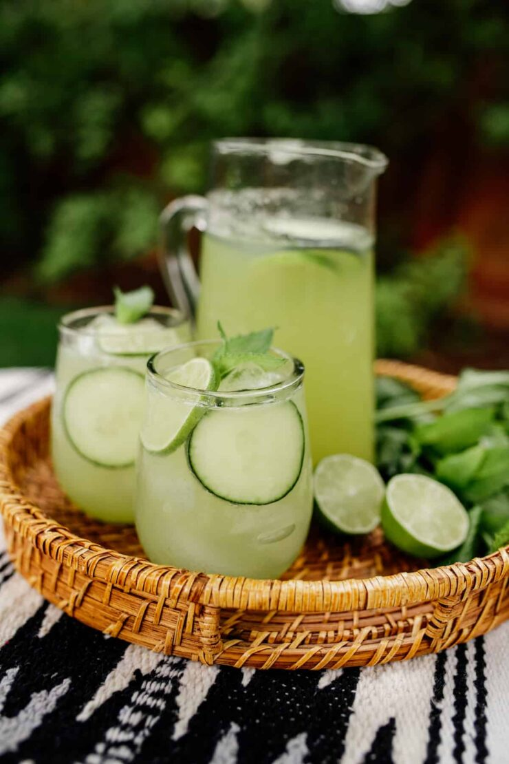 two glasses and a pitcher of cucumber agua fresca garnished with lime and mint