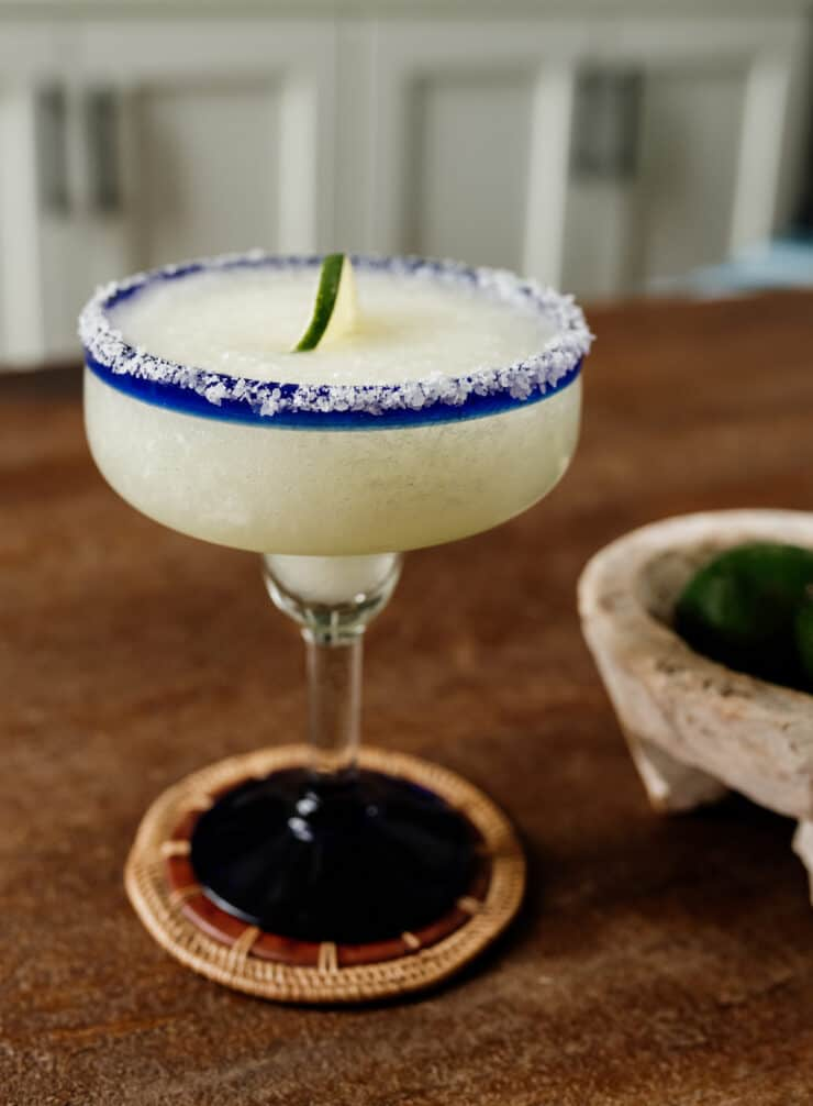 Classic Frozen Margarita with slated rimmed glasses top down with a side of limes