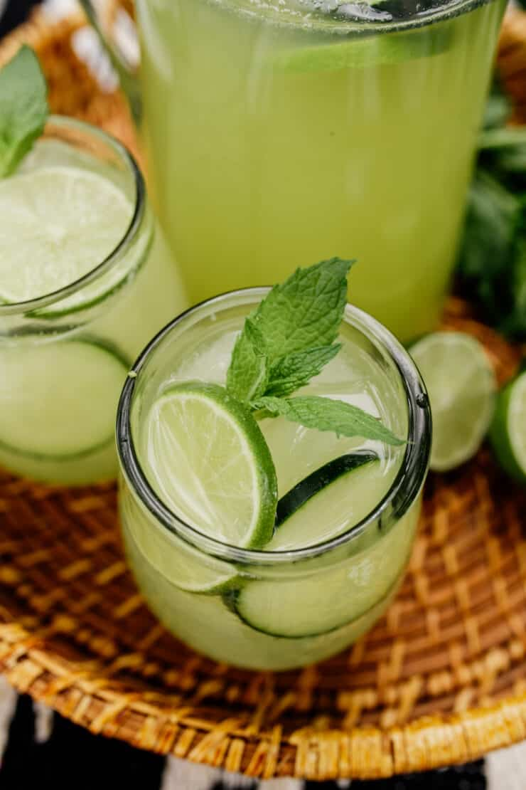 two glasses of agua de pepino garnished with mint and lime on a rattan serving tray