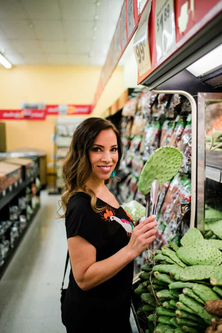 Yvette Marquez Denver Latina food blogger in a Latin grocery store holding a nopal with tongs