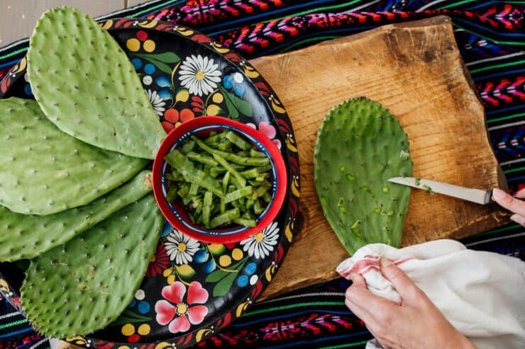 nopales whole and diced on a Colorado platter on a cutting board showing how to prep by removing spines