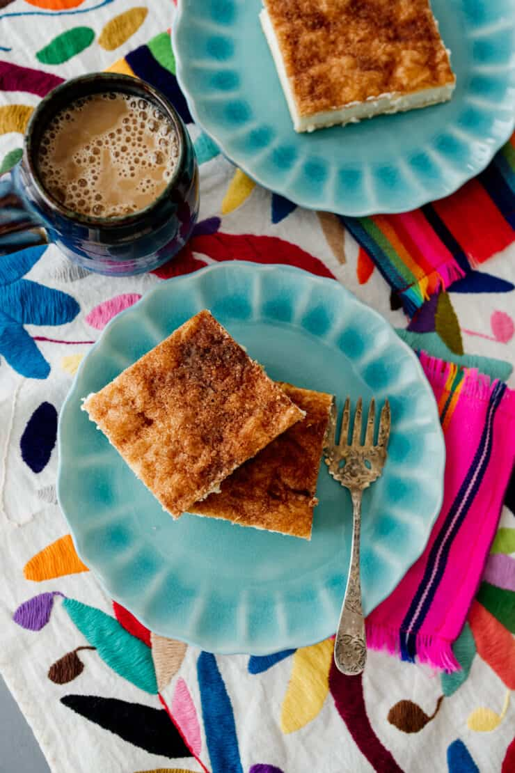 Sopapilla Cheesecake Bars on teal plates on a colorful textile on table with a cup of coffee