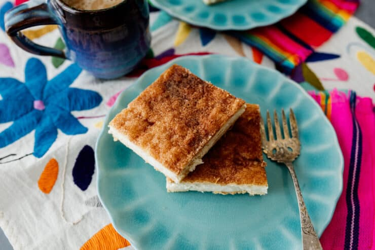 Sopapilla Cheesecake Bars or Churro Cheesecake Bars on a teal plate with a vintage fork on colorful linens