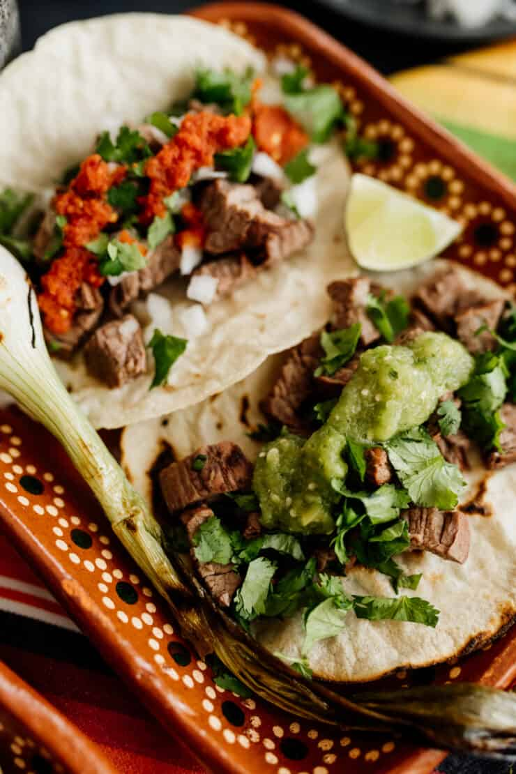 close up of a serving platter with carne asada tacos topped with two different kinds of salsa