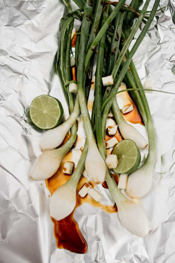 spring onions on a piece of foil with soy sauce and lime for grilling